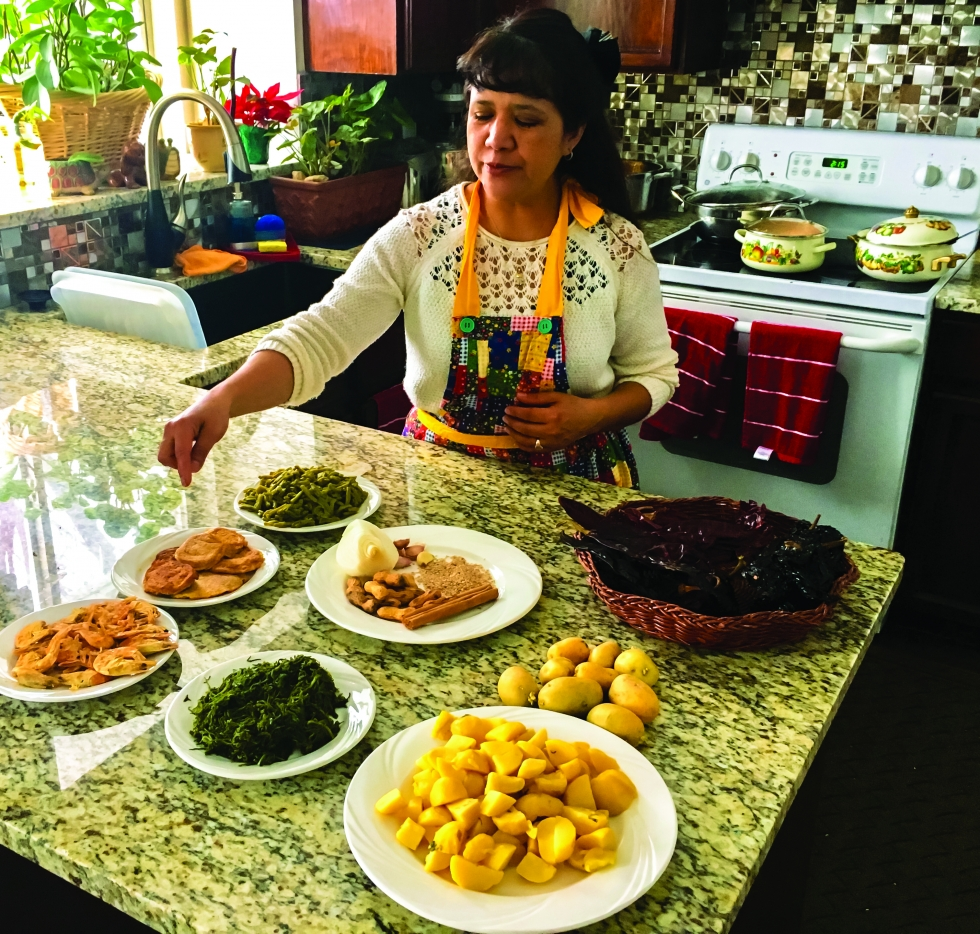 Gabriela Serrás prepares a dish of Aztec origin from central Mexico called Romeritos. This traditional Christmas and Easter dish consists of sprigs of romeritos – a wild seepweed plant that grows in marshy areas – potatoes, peanuts, dried shrimp and other spices in a mole sauce.  Photo by Charlotte Fife-Jepperson