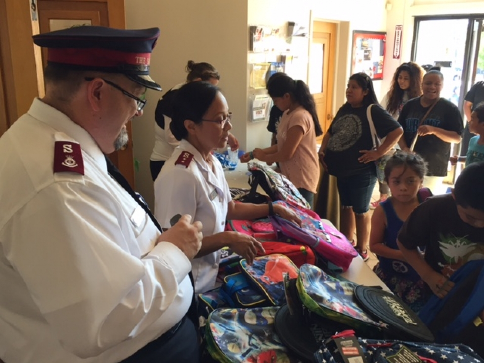 Salvation Army clergy hand out donated backpacks filled with school supplies to elementary school students from Salt Lake City's west side, Aug. 19.    Photo by Mike Dale