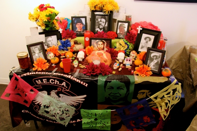 People often decorate their altar (ofrenda) with paper cutouts (papél picado), photos, traditional bread (pan de muertos), flowers (especially marigolds or cempasuchitl which were sacred to the Atecs), sugar skulls (calaveritas de ázucar) and other items that their loved ones enjoyed during life. Celebrants do not worship these altars; they are offerings in honor of their deceased loved ones.   By Miriam Florez|A young girl shows off her face paint, which is typically a combination of flowers and skulls, at a Día de los Muertos celebration at Mestizo Coffeehouse in 2013.  Photo by Miriam Florez|The making of colorful sugar skulls to signify a loved one who has passed is a common tradition during Día de los Muertos.   Photo by José Hernandez||||