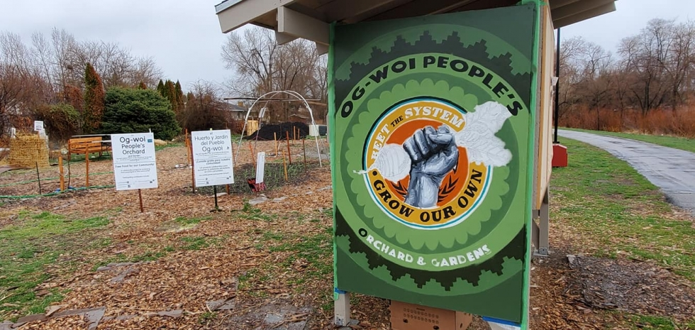 Volunteers paint the new logo on the kiosk in the Og-Woi People's Orchard in mid-March.