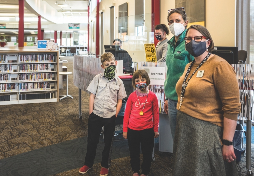 Glendale Branch Manager Brooke Young and staff, Saia Langi and Maria Campos, help a mother and her two children check out books on March 15, the day the city library started welcoming patrons back on a limited basis.