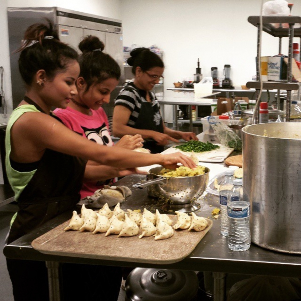 Entrepreneurs Kamal and Geeta make their vegetable samosas at Spice Kitchen in preparation for World Refugee Day Festival, held last summer at Liberty Park. Photo courtesy of Spice Kitchen Incubatoratering event.