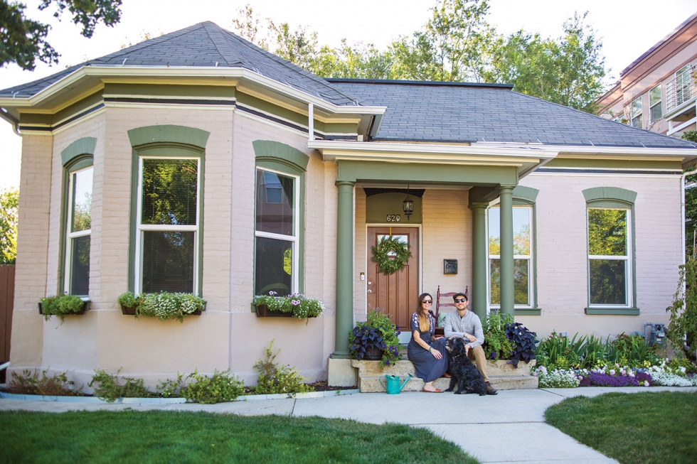 Amy Macintyre and Nick Pedersen, new owners of a 132-year-old home in Poplar Grove, pose on their front porch with their dog. They have been steadily working to improve the house and their quarter-of-an-acre yard.  Photo by Nick Pedersen