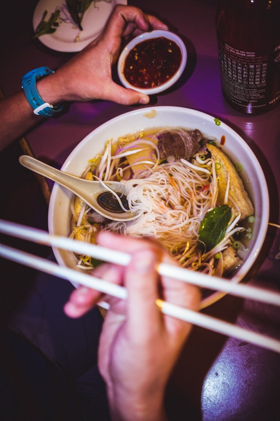 A satisfied customer dives into a large bowl of vegan Phô with noodles at All Chay.