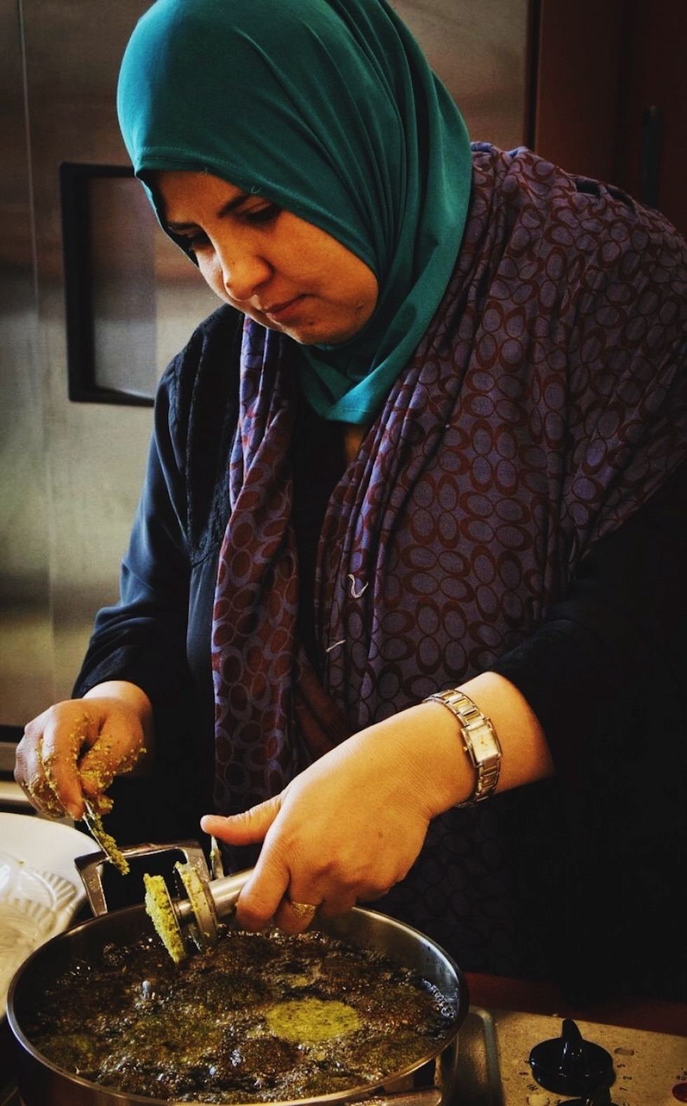 """An Iraqi woman drops a falafel croquette into hot oil for frying."" – from ""Savor – Stories of Community, Culture, and Food,"" page 26."