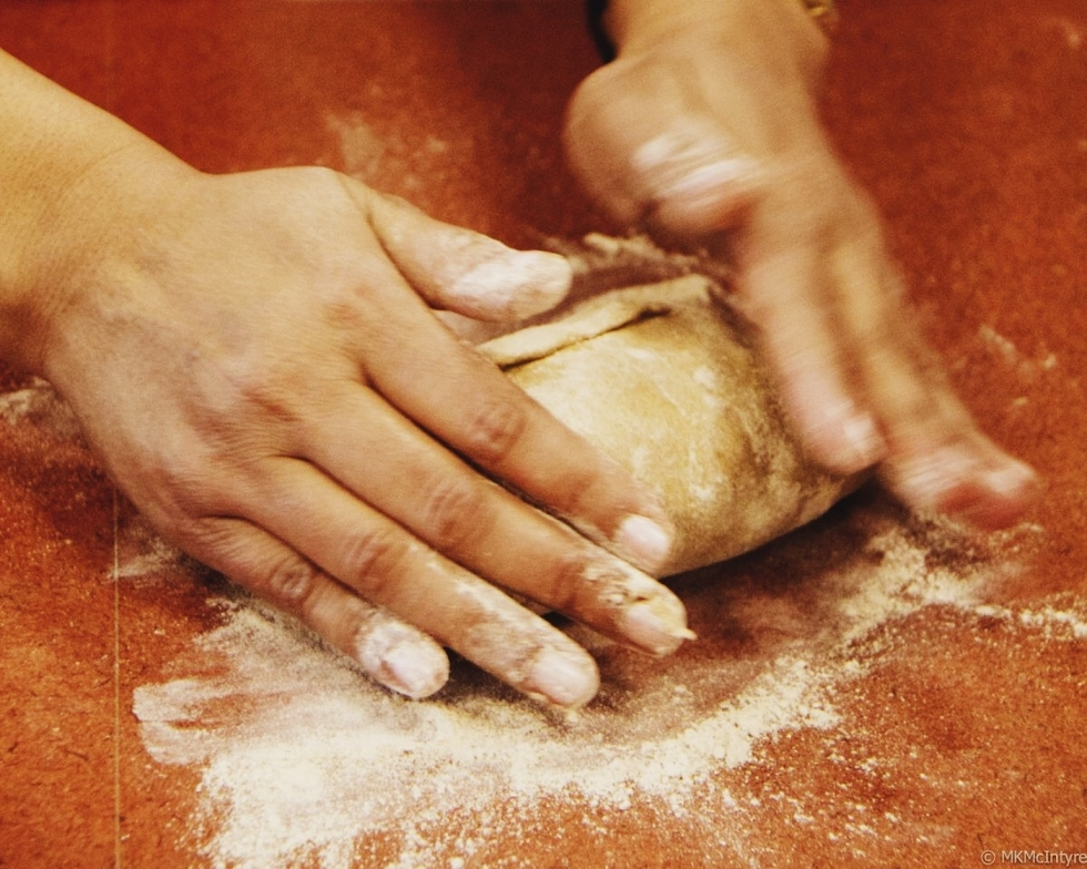 "Kabita Deo of Nepal prepares dough for aloo paratha, ""whole wheat flat bread stuffed with potatoes, cilantro, and spices, often eaten for breakfast in Nepal and India."" – from ""Savor – Stories of Community, Culture, and Food,"" p.46."