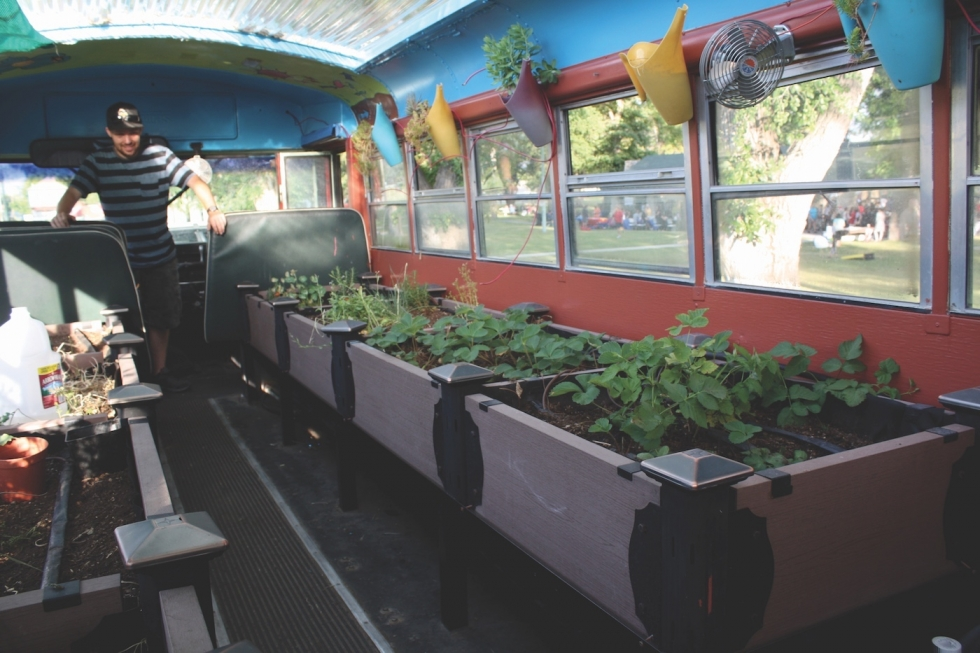Aaron Porter from Green Urban Lunchbox shows off the school bus that they modified into a mobile garden at Jordan Park during a summer event put on by University Neighborhood Partners.