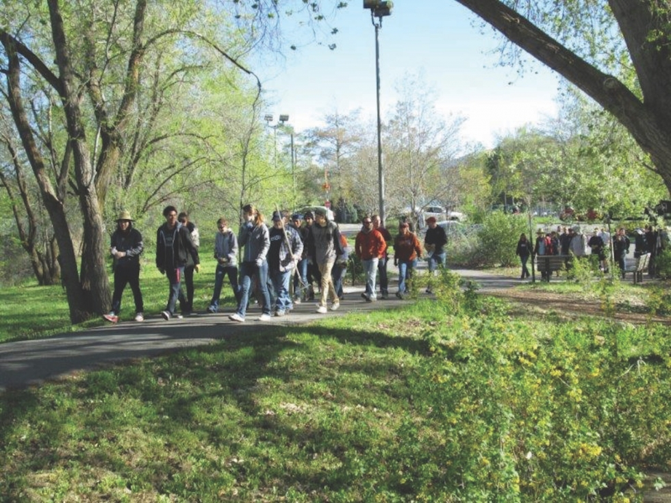 Volunteers walk toward the Bend in the River section along the Jordan River Parkway Trail in Glendale.