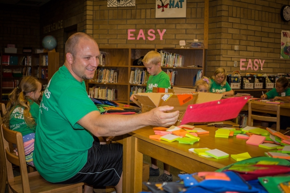 Chris Ulrich tosses a pencil pouch after filling it with the help of his daughters. Ulrich and other volunteers spent Saturday morning in the Jackson Elementary Library preparing 500 binders for students in the coming school year.
