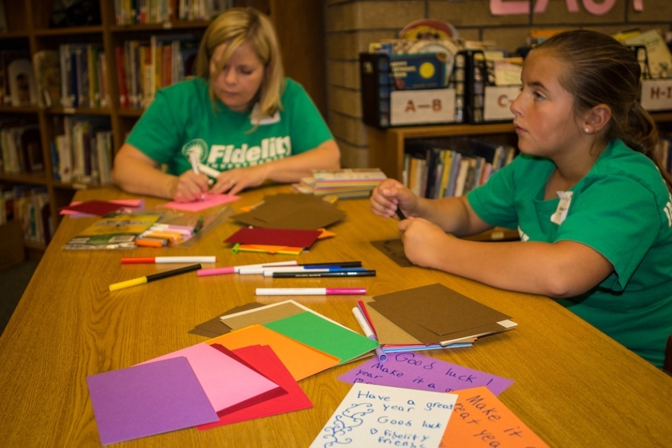Stacy Schmalz and her daughter Delanie write inspirational notes to insert into 500 binders that they helped assemble in Jackson Elementary's library on June 20th for the Fidelity Cares School Transformation Day.