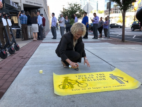 Salt Lake City Mayor Jackie Biskupski paints a stenciled safety message onto a downtown sidewalk at an October safety event.|Representatives from Bird give out helmets to the public during a safety press conference event in October||||