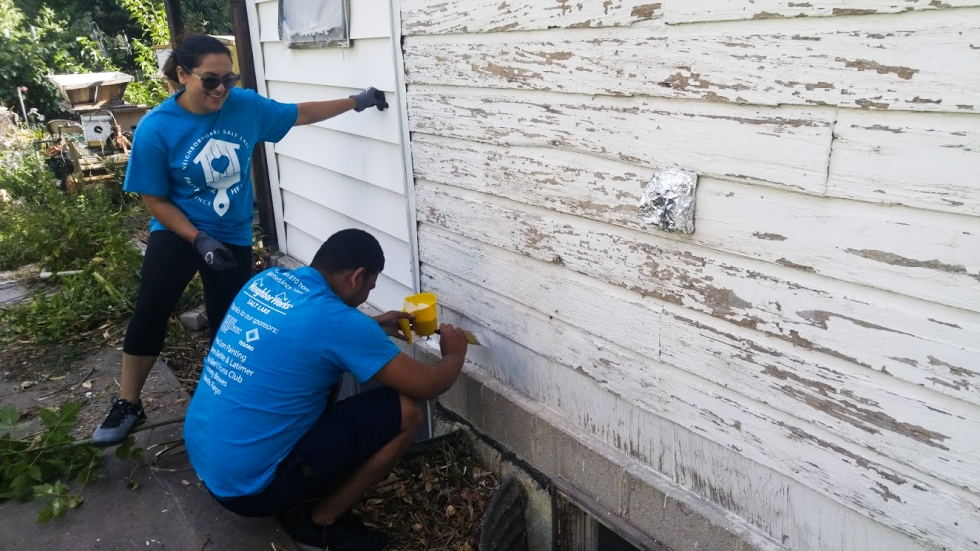 In 2017, two Paint Your Heart Out volunteers receive training and professional assistance throughout the process of painting the exterior of a home.