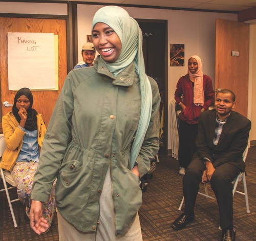 Aysha Mohamed takes a turn in the center of the circle at a recent ice-breaker activity at the Hartland Partnership Center, where participants in Youth Voices meet. Pictured in the back (from left to right) are: Islam Ibrahim, Siosia Langi (facilitator), Rahma Mustafa and Jeilani Athman (faciltator).|Left to right: Esperance Iradukunda, Manarigo Lenata, Emmanuel Rokondo pose for a photo during an ice-breaker activity at the Hartland Partnership Center in December of last year.|:  Participants in Youth Voices at UNP's Hartland Partnership Center pose for a photo. Back row, from left to right: Siosaia Langi (facilitator), Emmanuel Rokondo, Aysha Mohamed, Ismahan Mohamed, Islam Ibrahim, Rahma Mustafa, Omar Bakari, Jeilani Athman (facilitator). Front row: Manarigo Lenata (mentor), Esperance Iradukunda, Aurelia Rodriguez, Fatma, Maricela Hernandez (mentor)||||