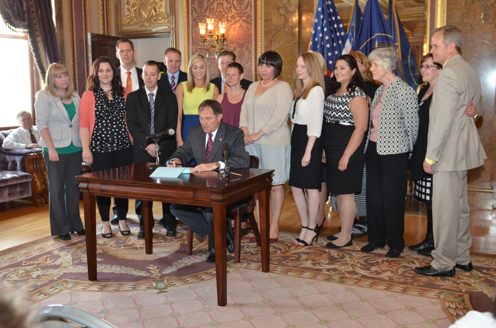 Governor Gary Herbert officially signed HB 286 into law on April 1, 2014. Present at the signing were (from left to right): Carrie Jensen, Kristin Parry, Rep. Jacob Anderegg, Preston Jensen, Rep. Craig Hall, Ciera Pekarcik (Miss Utah 2013), Senator Todd Wiler, Alana Kindness, Rep. Angela Romero, Deondra Brown Nielsen, Alexis Santoyo, Pamela Atkinson, Trina Baker Taylor and Ed Smart. You can also see the back of Rep. Marie Poulson and Minority Leader Jennifer Seelig's heads.