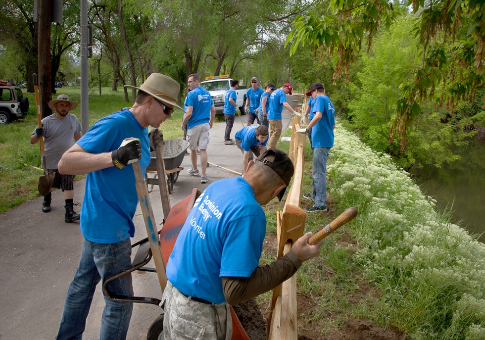 A group of Dominion Energy employees help install a split rail fence last year along the Jordan River Parkway trail between 200 South and 500 South in a section adopted by the company.                                      Photo courtesy of Darren Shepherd, Dominion Energy