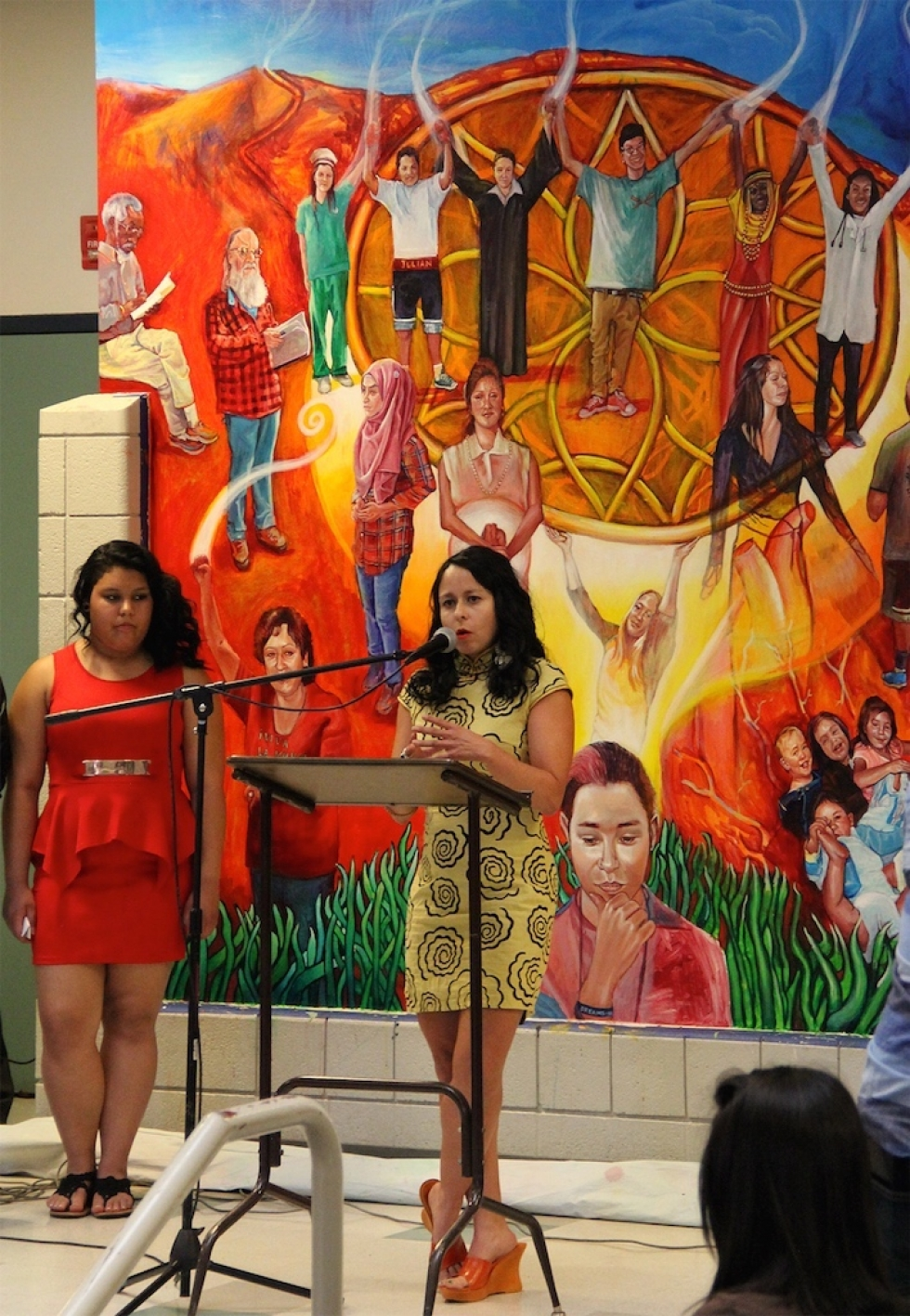 """Ruby Chacon, a product of the west side and proud alumnist of Horizonte School, speaks at the unveiling of """"Pursuit of Dream(ers),"""" her latest mural on Horizonte's second floor. The artwork features portraits of past, but mostly present students. Twenty people were involved in the making of the mural."""