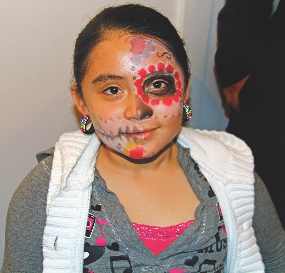 A young girl shows off her face paint, which is typically a combination of flowers and skulls, at a Día de los Muertos celebration at Mestizo Coffeehouse in 2013.  Photo by Miriam Florez