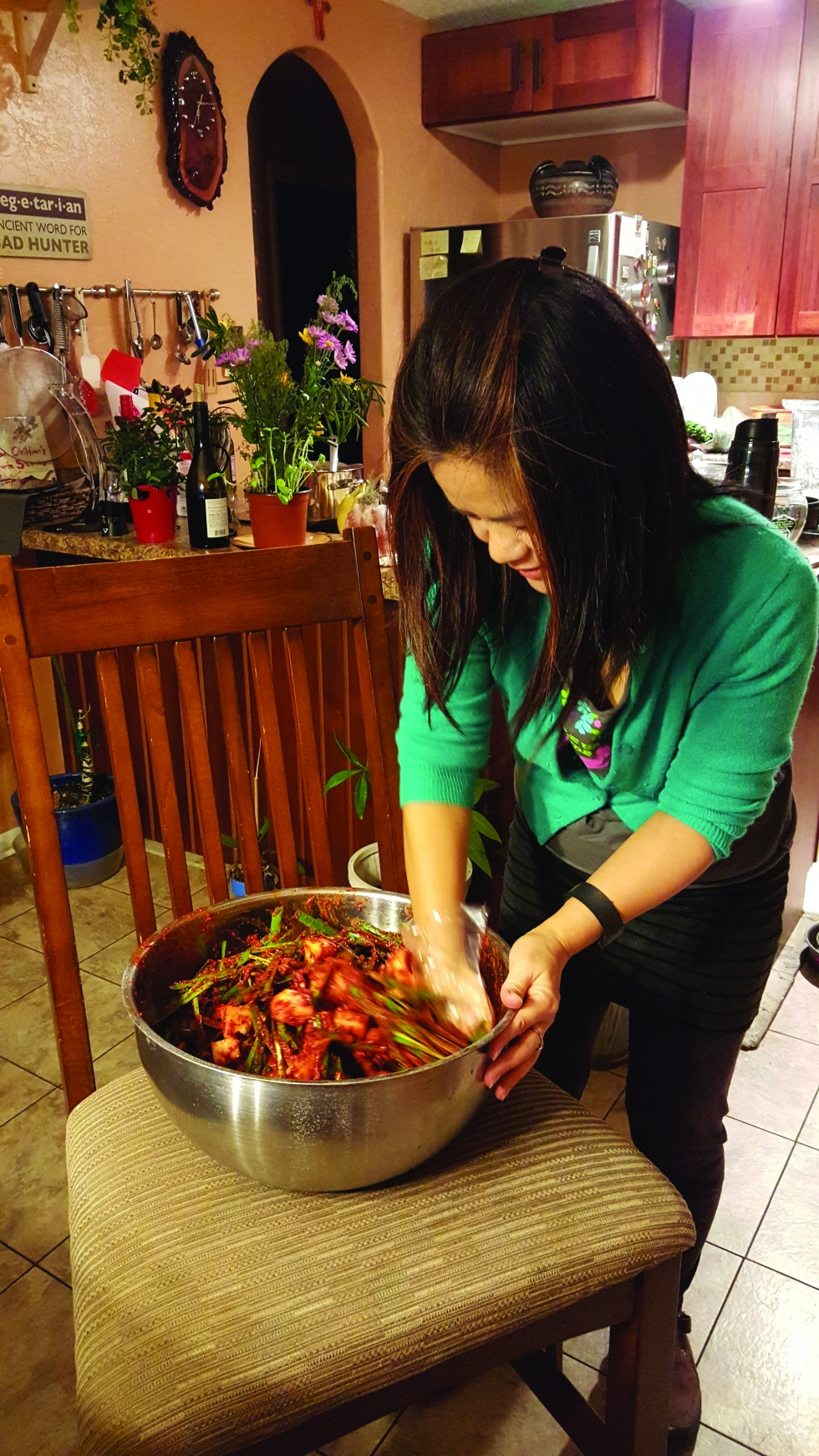Jaehee Yi mixes the ingredients for kimchi in her Rose Park kitchen. Photo by Gabriela Cetrola