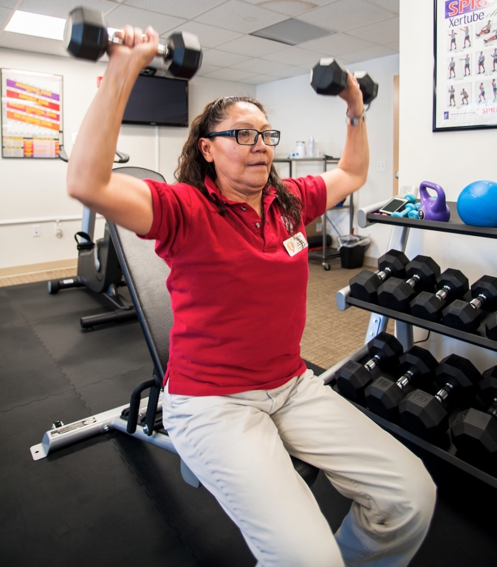 Certified Personal Trainer Gay Dawn Pinnecoose spots her daughter and Youth Program Coordinator, Penelope Pinnecoose, as she does a dumbbell chest press at the Urban Indian Center of Salt Lake.