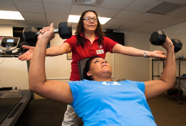 Certified Personal Trainer Gay Dawn Pinnecoose demonstrates a seated dumbbell chest press at the Urban Indian Center of Salt Lake, where she works.|Certified Personal Trainer Gay Dawn Pinnecoose spots her daughter and Youth Program Coordinator, Penelope Pinnecoose, as she does a dumbbell chest press at the Urban Indian Center of Salt Lake.|||