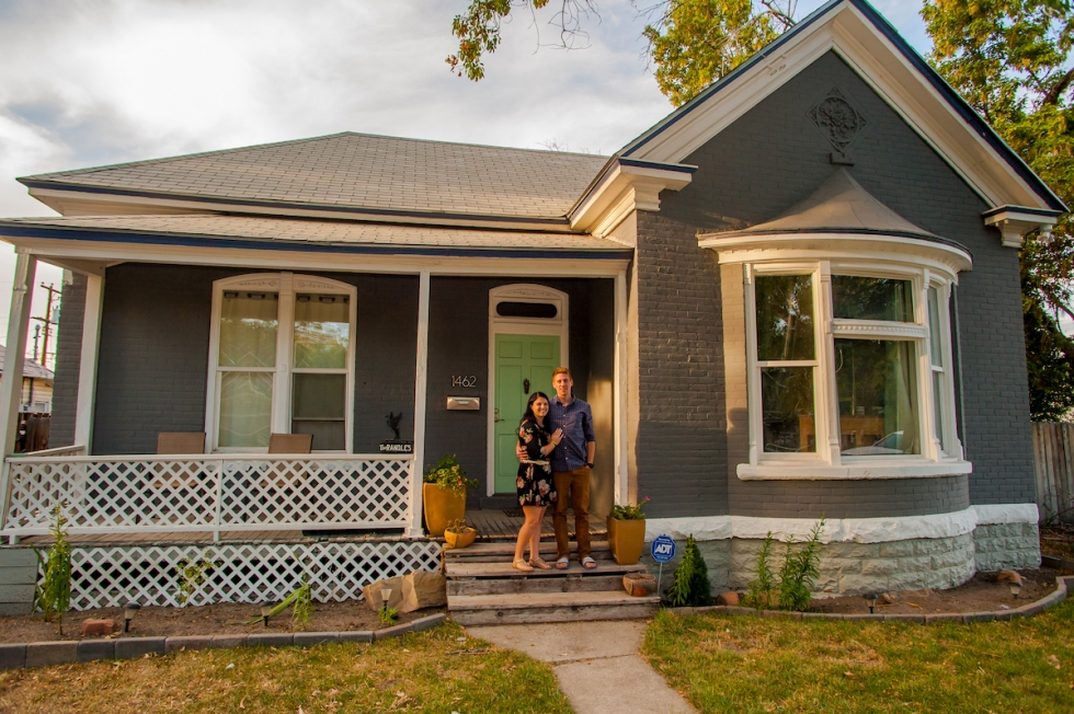 Taylor and Ramie Randle pose in front of their 1912 home, which is up for sale in Poplar Grove.