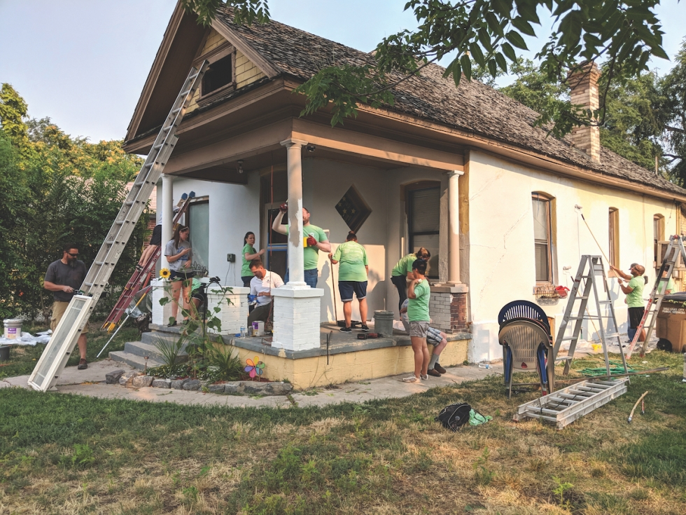 Volunteers from Veritas Funding Old Mill paint Skylar and Shain Shield's 100-year-old Poplar Grove home during the 2018 Paint Your Heart Out event. Shain, a disabled veteran, and his wife Skylar welcomed identical twins last summer.