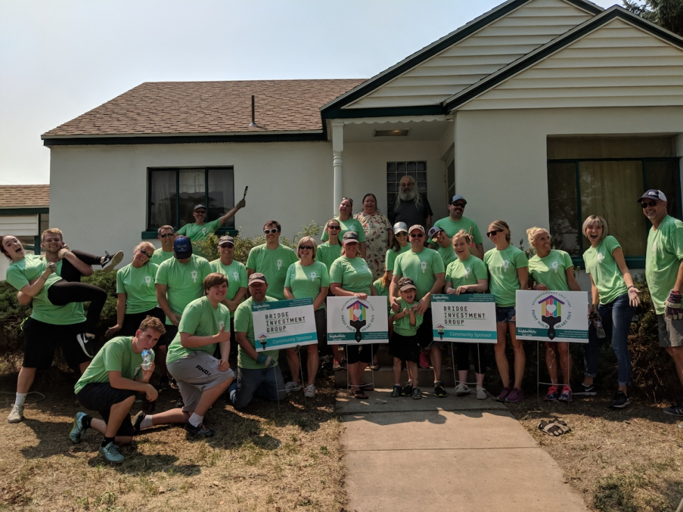 Bridge Investment Group volunteer team pose in front of the Shelton's Fairpark home after they worked all morning putting a fresh coat of paint on it during the 2018 Paint Your Heart Out event.