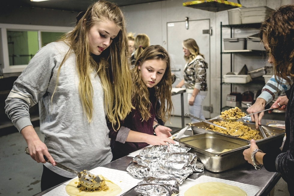 Volunteers prepare burritos at the Rico Brand warehouse to feed hungry and homeless people in Salt Lake City.  Photo by Daniel Lombardi