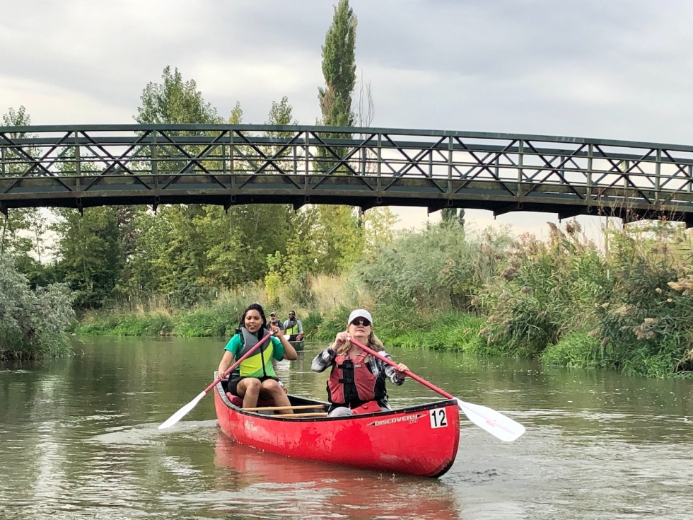 Jasmine Walton and Connie Lanier navigate the Jordan River in a canoe during a team-building activity for their work at NeighborWorks Salt Lake last summer.   Photo by Charlotte Fife-Jepperson