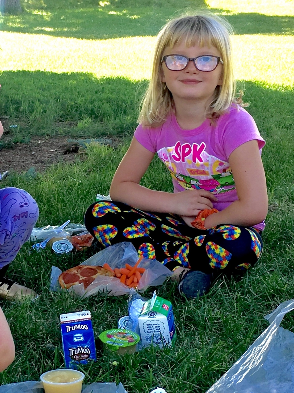Rayme, age 6, happily eats her free lunch of pizza, veggies, applesauce and milk, in the shade at Sherwood Park on July 1.