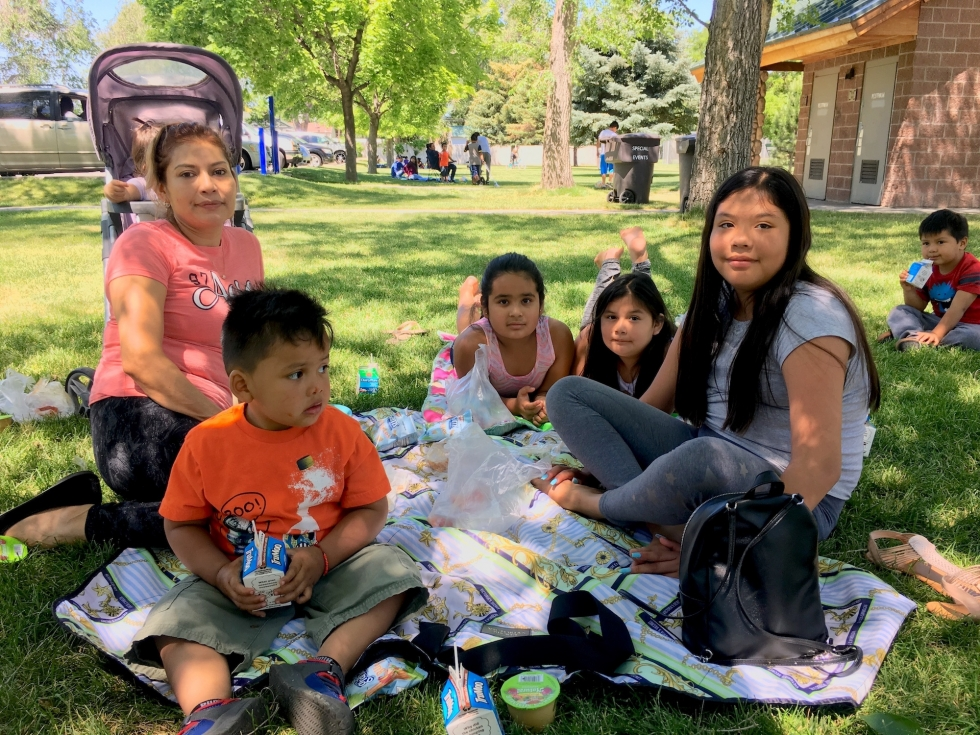Maggie Hernandez eats lunch at Sherwood Park with her three children and four others that she tends. They enjoy free meals at the park almost daily during the summer.