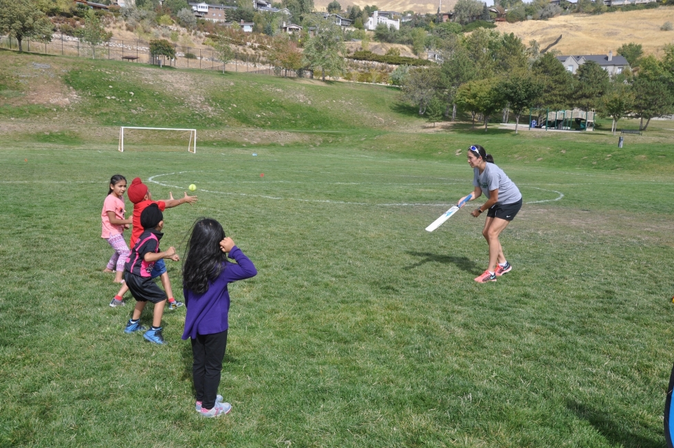 Volunteer Jenn Goodrum instructs children in the basics of cricket at the Utah Cricket Association's Youth Camp last year at 11th Avenue Park. Photo courtesy of Utah Cricket Association