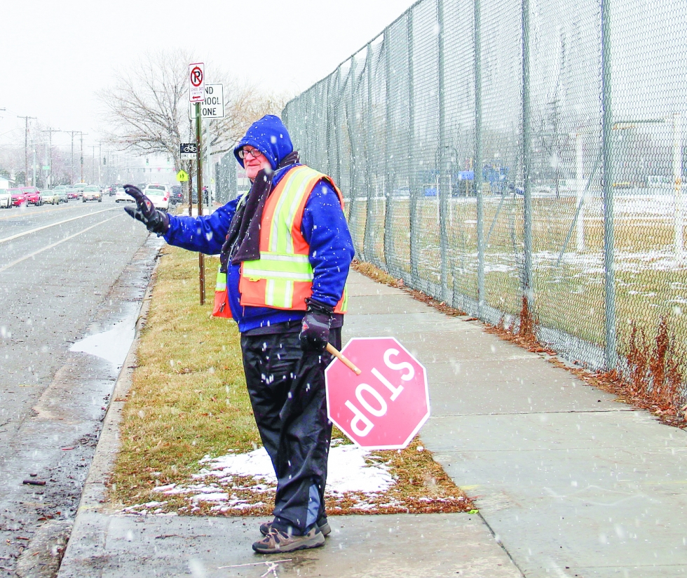 Photo caption: Despite snowy weather, crossing guard Kevin Bunting acknowledges passersby in front of Mountain View Elementary with his trademark friendly wave. Photo by Michael Evans
